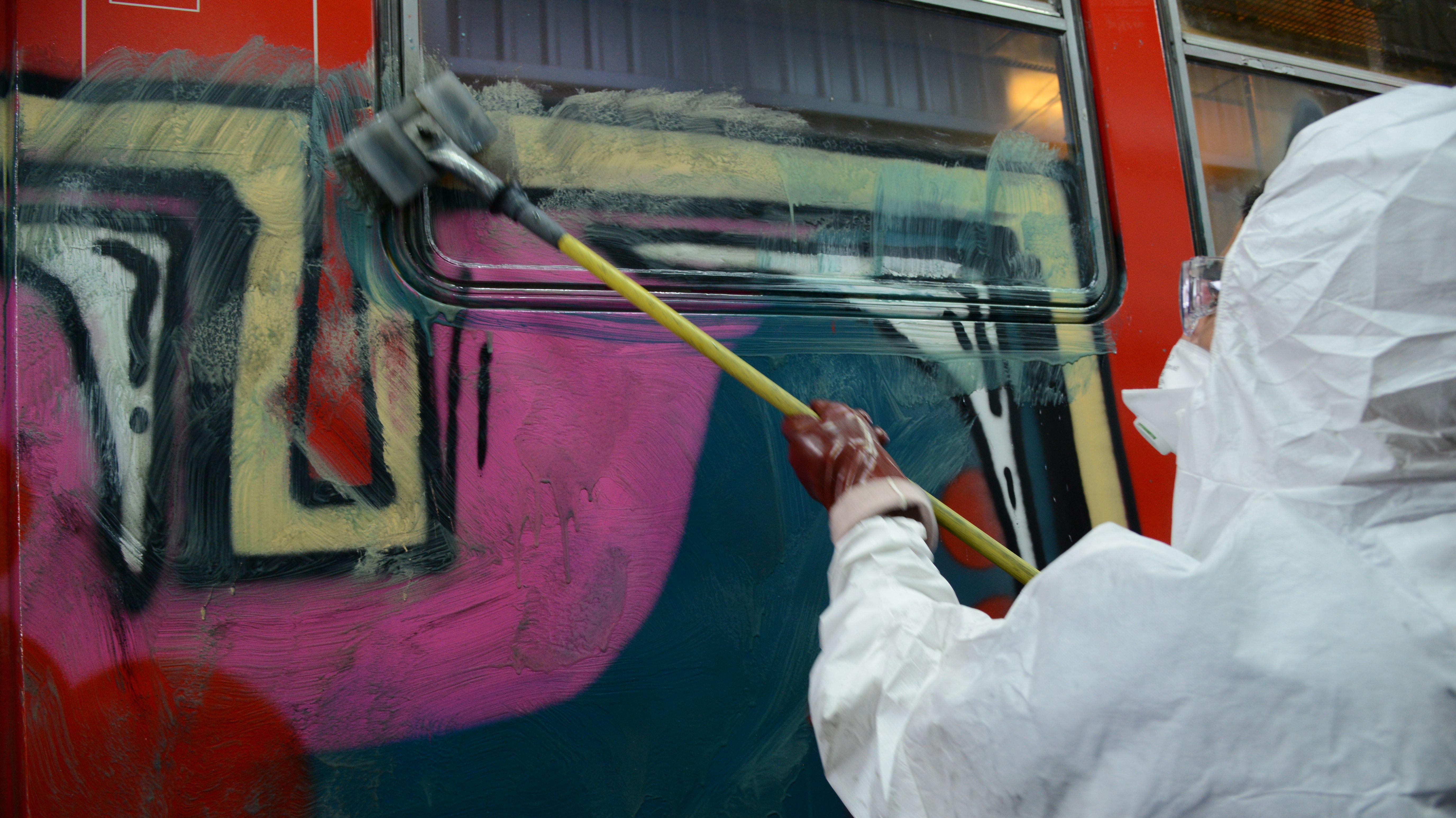 Ein Mitarbeiter der Bahn entfernt ein Graffiti von einem Zug.