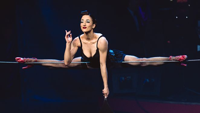 Eine Akrobatin macht einen Spagat auf einem Seil. Sie ist im Look des Varieté der 1930er-Jahre gestylt.
