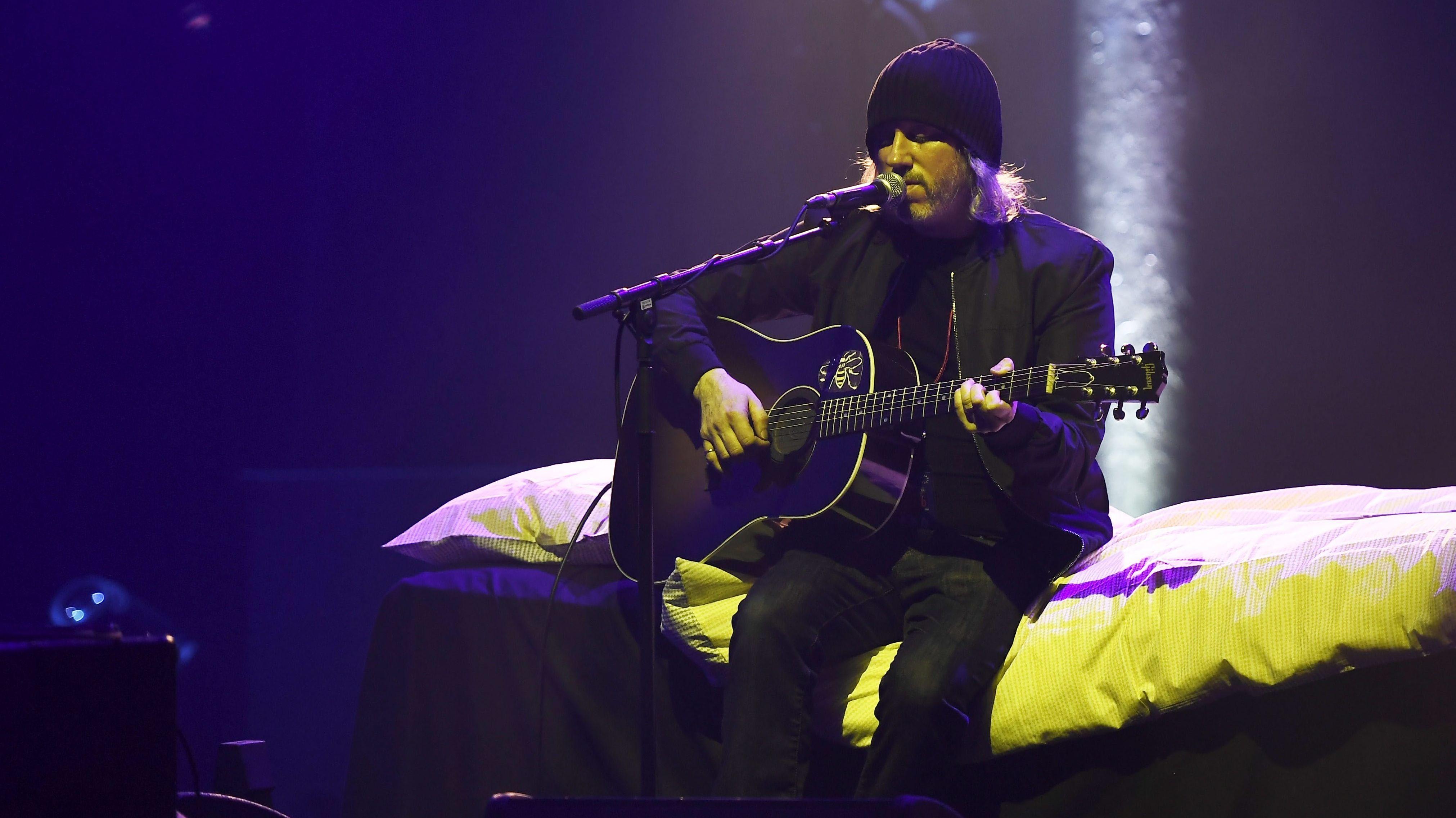 Ein Mann mit Gitarre in einem tiefblauen Raum sitzt mit Mütze auf einem Bett mit leuchtend gelber Decke