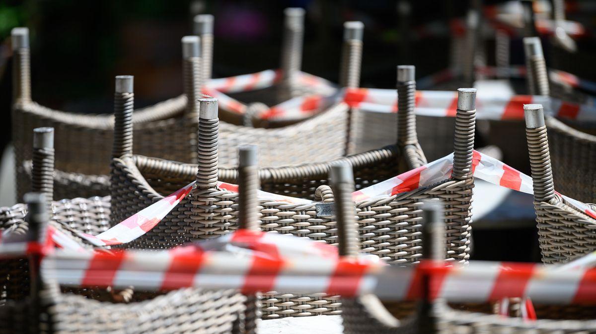 Stuttgart: Gestapelte Stühle sind mit Absperrband im Bereich eines Restaurants gesichert.
