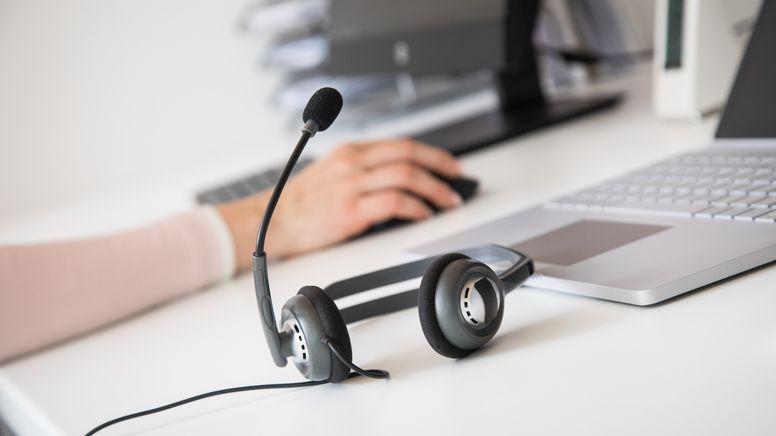 Ein Headset liegt neben einem Laptop auf einem Schreibtisch   Bild:picture alliance / dpa-tmn   Christin Klose