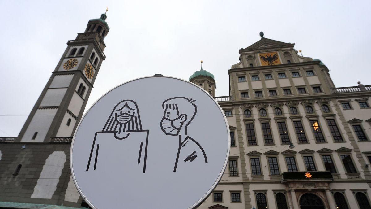 Das Augsburger Rathaus aus Froschperspektive. Davor ein helles Hinweisschild zur Tragepflicht von Nase- und Mundbedeckungen