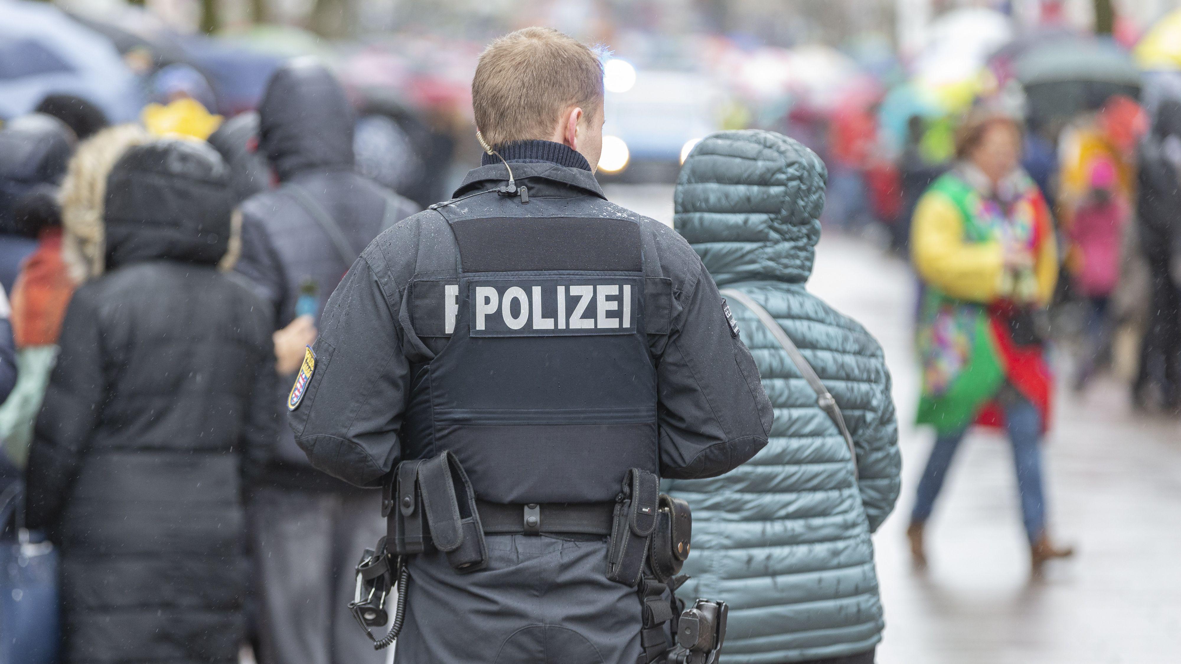 Ein mit dem Rücken zum Betrachter stehender Polizeibeamter steht vor einer Menschenmenge.