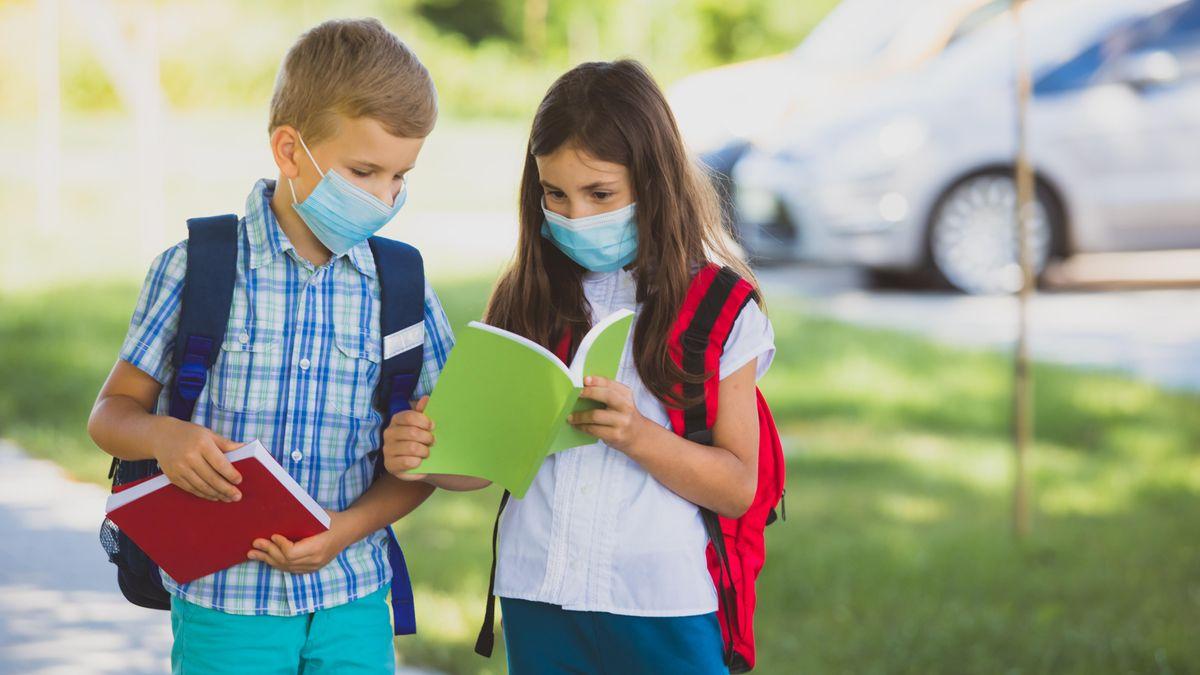 Ein Mädchen und ein Junge tragen beide Maske unter zeigen sich gegenseitig etwas in einem Schulheft.