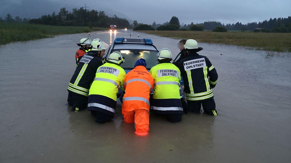 Auf der überschwemmten Bundesstraße B 2 zwischen Murnau und Ohlstadt ist ein Polizeiauto in den Wassermassen halb versunken.
