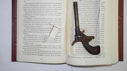 Buch mit Pistole | Bild:Polizeiinspektion Flughafen München