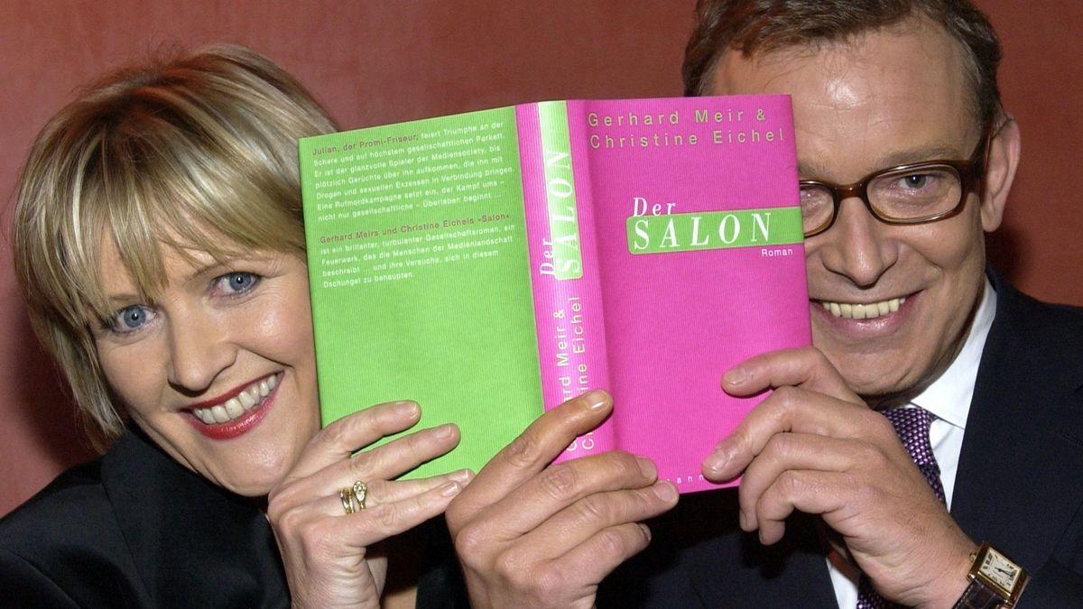 """Lachend hält Gerhard sein gemeinsam mit der Schriftstellerin Christine Eichel verfasstes Buch """"Der Salon"""" in die Höhe."""