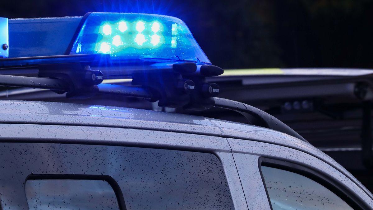 Zwei Polizeifahrzeuge mit eingeschaltetem Blaulicht stehen schräg versetzt an einer Einsatzstelle (Symbolbild).
