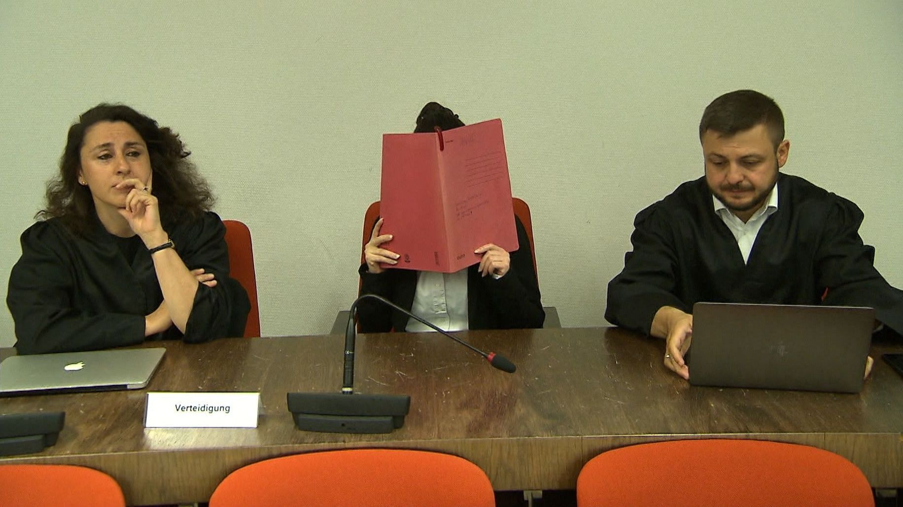 Die Angeklagte Jennifer W. hält sich einen roten Ordner vors Gesicht, rechts und links neben ihr sitzen ihre Verteidiger.