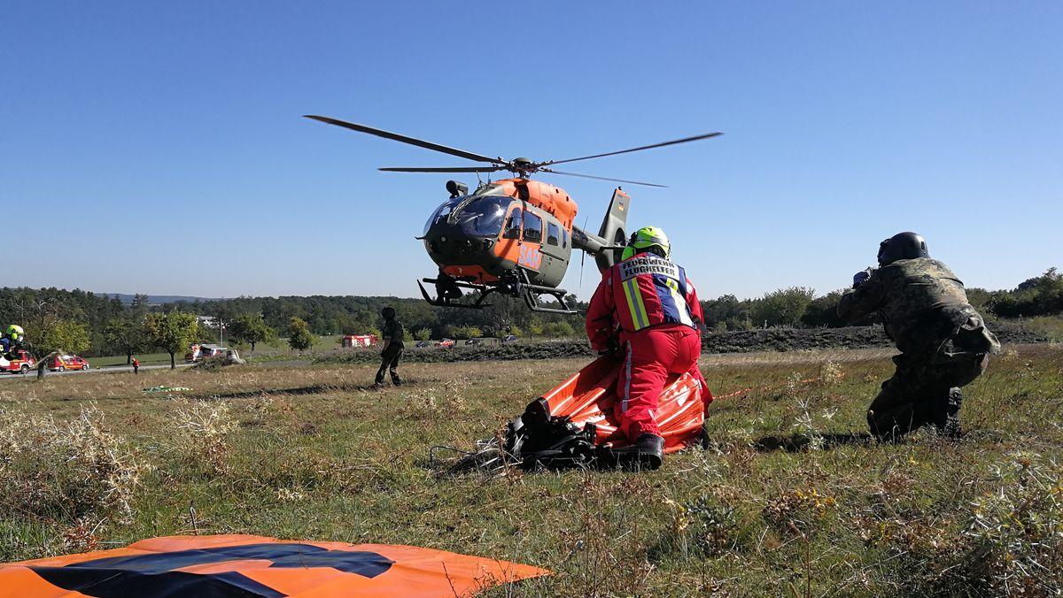 Ein Feuerwehrmann und ein Soldat vor einem Hubschrauber beim Lehrgang