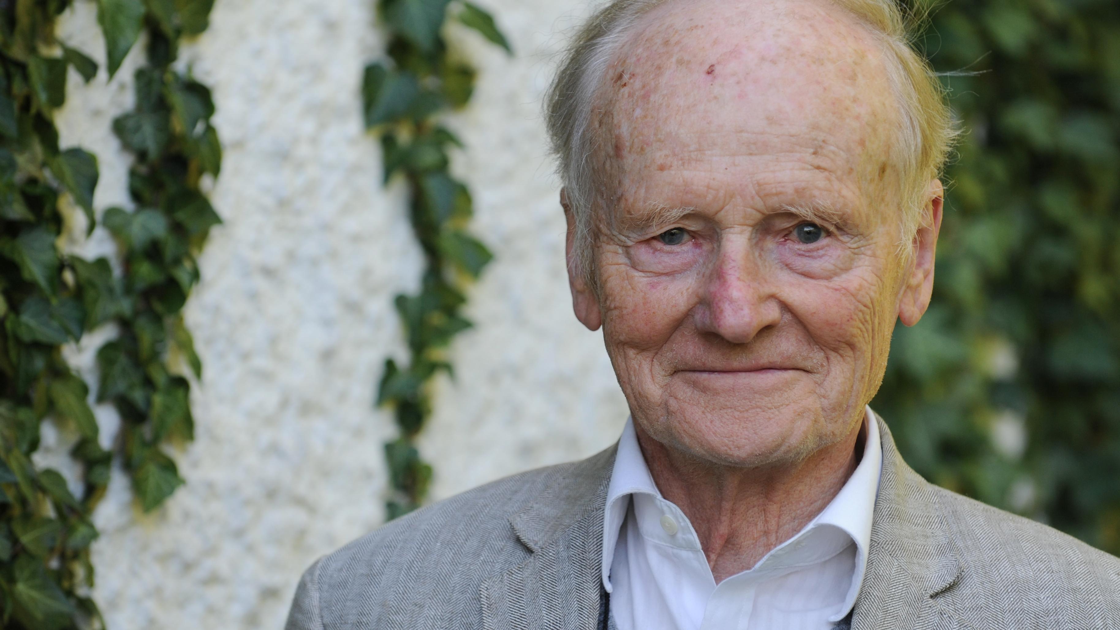 Philosoph Robert Spaemann lächelt vor einer von Efeu bewachsenen Mauer in die Kamera