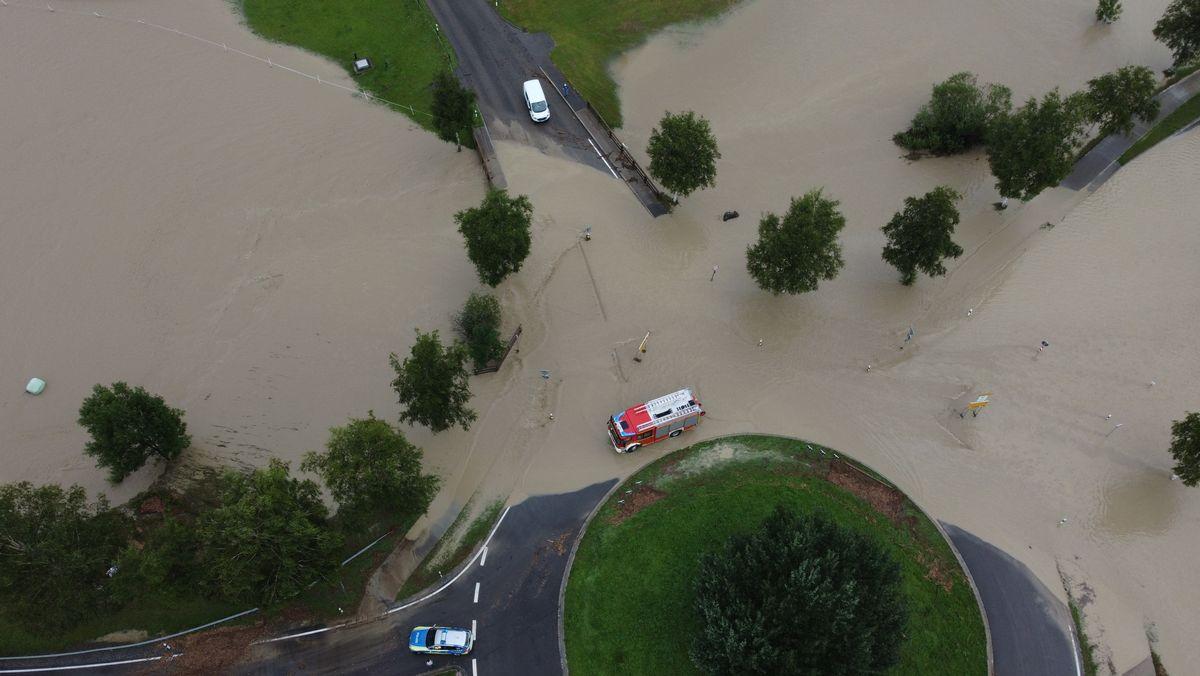 Rettenberg: Ein Feuerwehrfahrzeug fährt durch das hoch stehende Wasser an einem Kreisverkehr vor dem Ort.