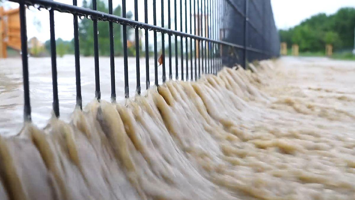 Bei einer Überschwemmung in Wertingen fließen braune Wassermassen durch einen Zaun.