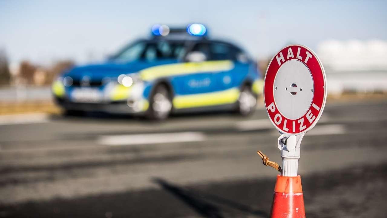 """Eine Polizeikelle mit der Aufschrift """"HALT POLIZEI"""" steht an einer Landstraße vor einem Polizeiauto der Münchner Polizei"""