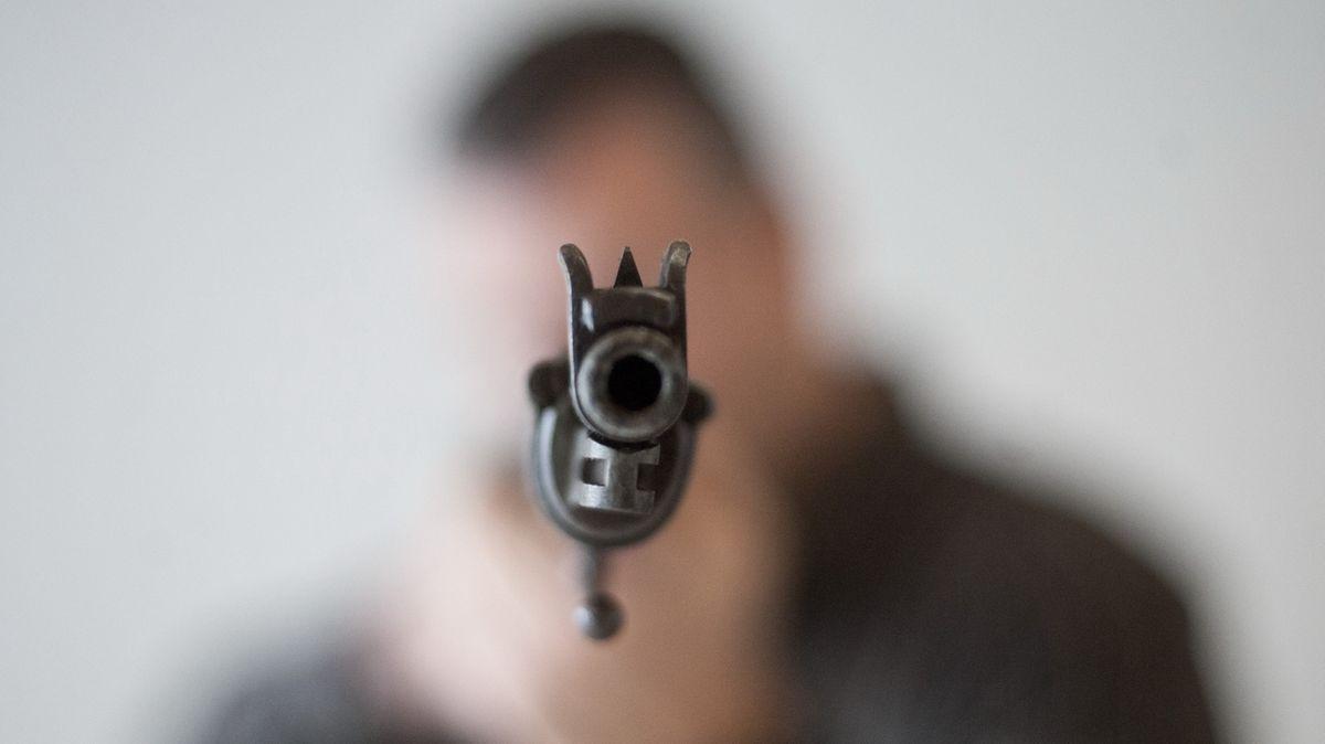 Ein unscharfer Mann im Hintergrund hält eine Waffe in die Mitte des Bildes. (Symbolbild)