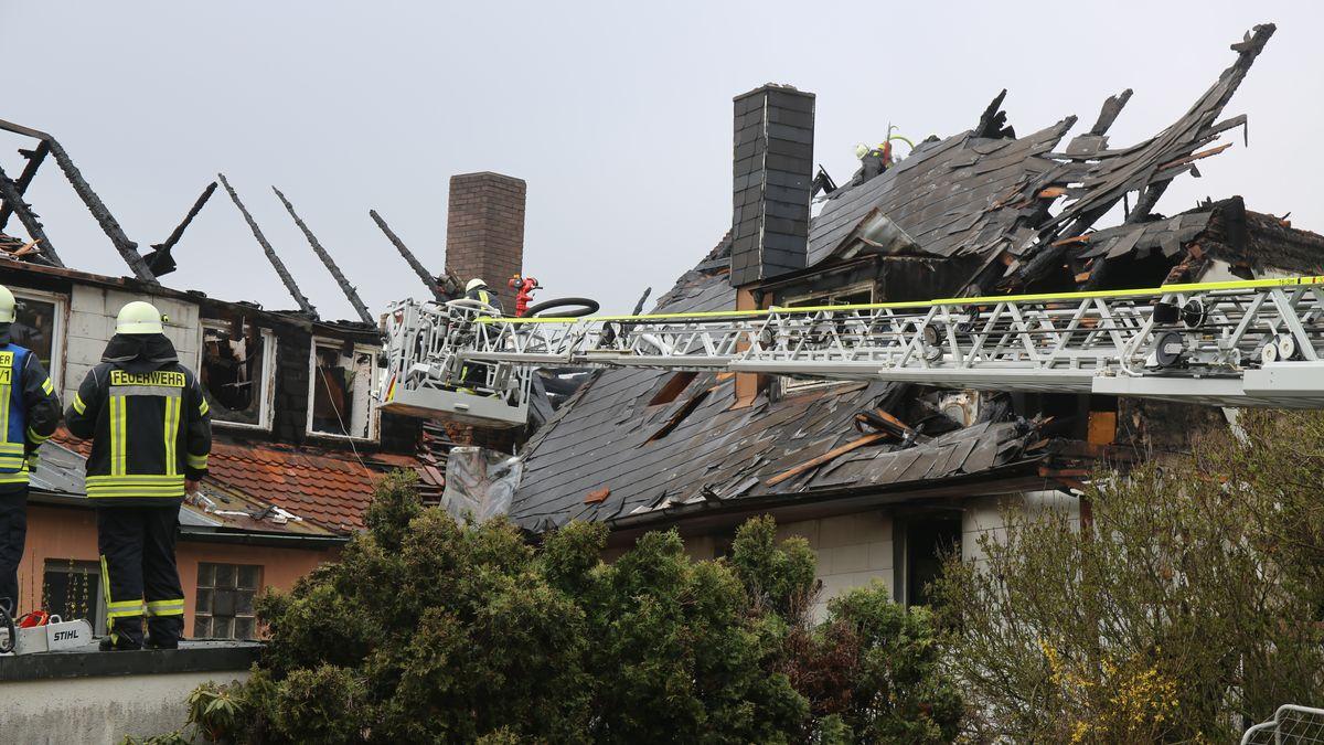 Feuerwehrleute stehen auf eine Feuerleiter vor zwei ausgebrannten Dachstühlen.