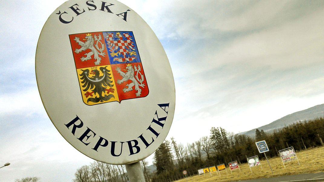 """An der Deutsch-Tschechischen Grenze ein Schild """"Ceska Republika"""" mit viergeteiltem Wappen."""