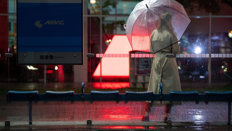 Frau im Regen an einer Münchner Bushaltestelle