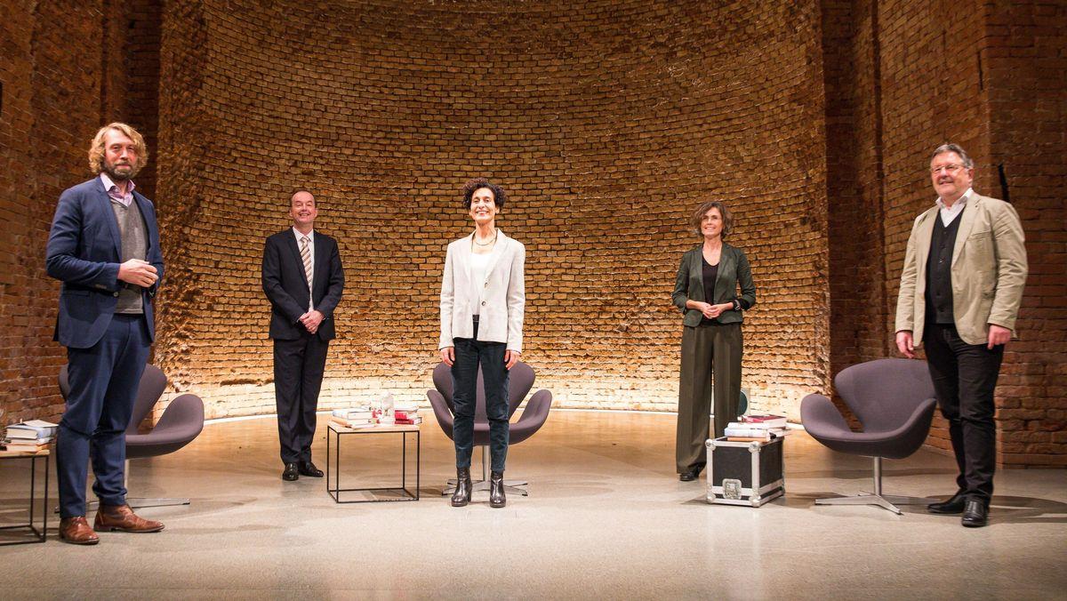 Jury, Moderatorin und Vorsitzender des Börsenvereins des Deutschen Buchhandels Bayern stehen in der Apsis der Allerheiligen-Hofkirche