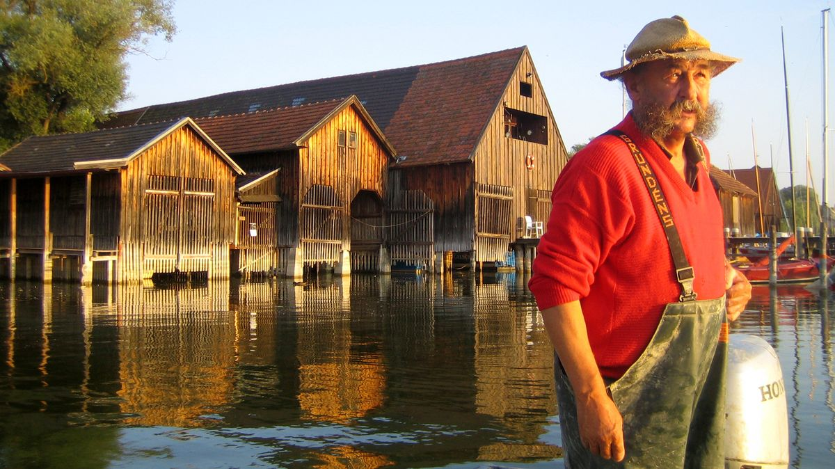 Der Fischer Simon Rauch vor  Bootshütten auf dem Ammersee