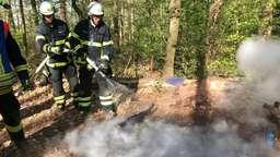 Zwei Feuerwehrmänner der Freiwilligen Feuerwehr Volkach löschen mit dem Schlauch ein immer noch schwelendes Lagerfeuer mitten im Wald.   Bild:Feuerwehr Volkach/Foto: Moritz Hornung
