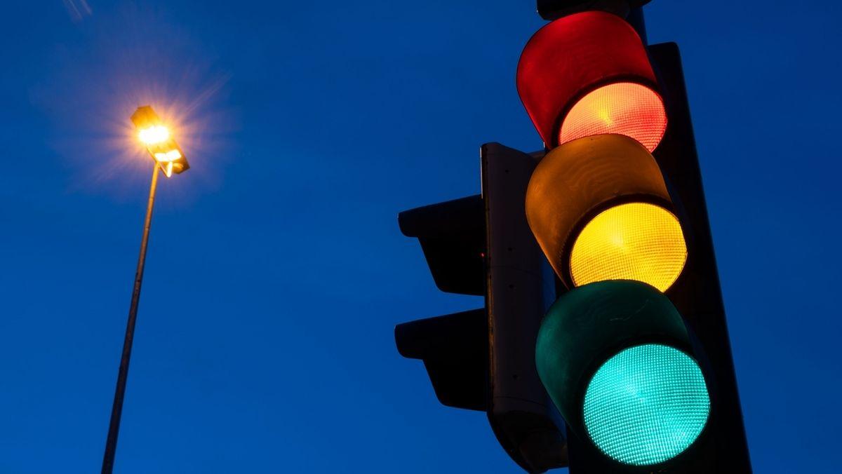 Eine Ampel zeigt am frühen Morgen die Farben rot, gelb und grün
