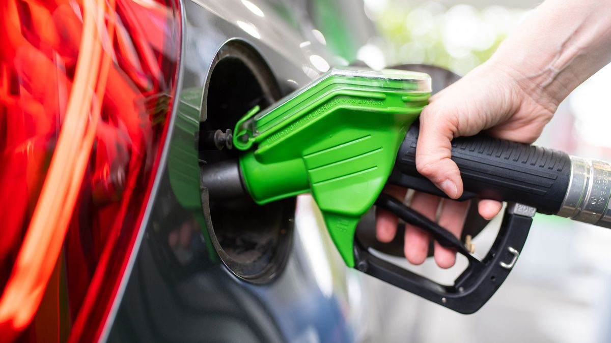 Eine Frau hält an einer Tankstelle an einer Zapfsäule eine Zapfpistole in der Hand und betankt ein Auto.