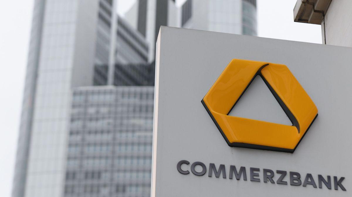 Das Schild einer Commerzbank-Filiale ist an einer Hausfassade nahe der Zentrale der Commerzbank angebracht, die im Hintergrund zu sehen ist.