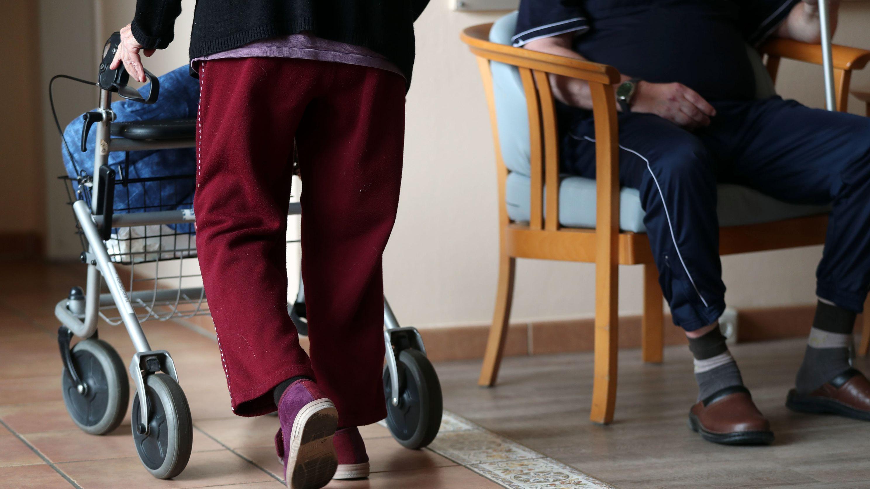 Eine ältere Frau geht mit einem Rollator über den Flur eines Pflegeheims in Mecklenburg-Vorpommern.
