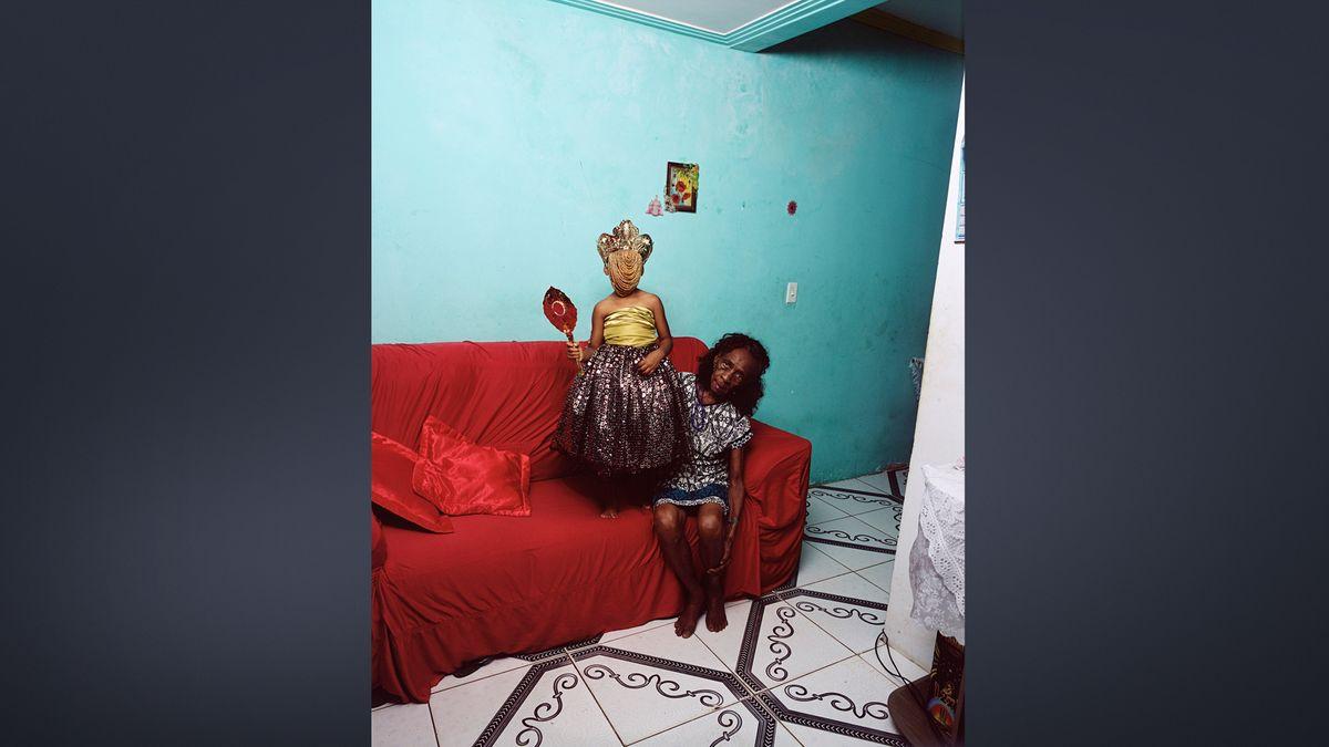 """Fotografie """"An Ode to Yemaya"""" (2019): Alte Frau sitzt auf einem Sofa, neben ihr steht auf dem Polster ein kleines Mädchen in festlichem Kleid, Kopfschmuck und Gesichtsverhüllung"""