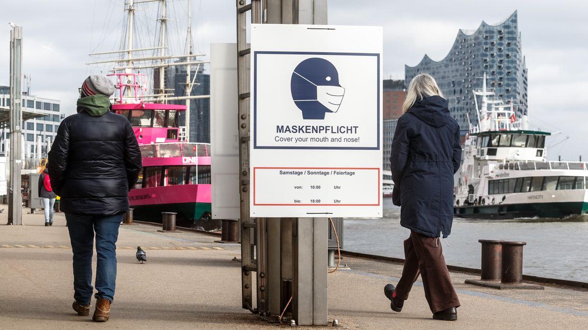 Ein Hinweisschild zur Maskenpflicht hängt auf den Landungsbrücken an der Elbe in Hamburg.