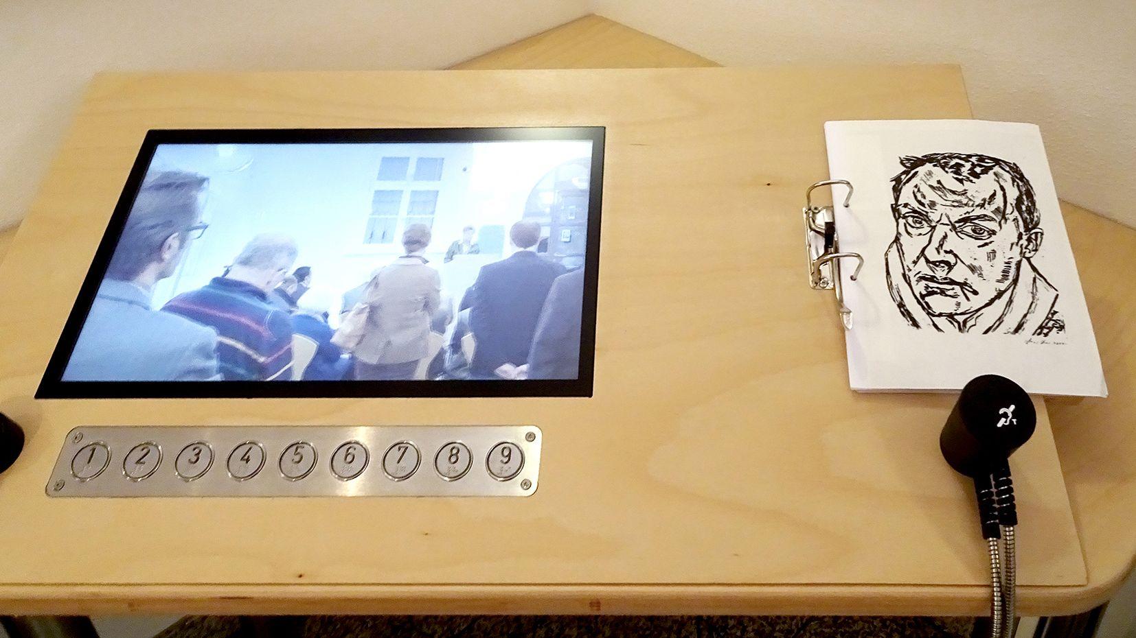 Inklusive Info-Station im Kunstmuseum Bayreuth: Bildschirm, Steuertasten und ein Ordner mit Bilder-Tast-Modellen für Sehbehinderte