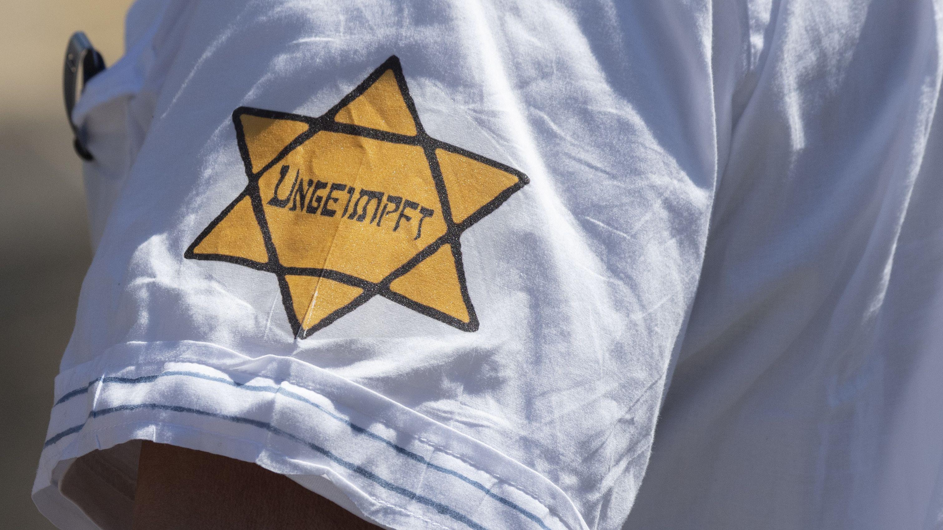 """Archivbild:  """"Ungeimpft"""" steht auf einem nachgebildeten Judenstern am Arm eines Mannes auf einer Demonstration"""