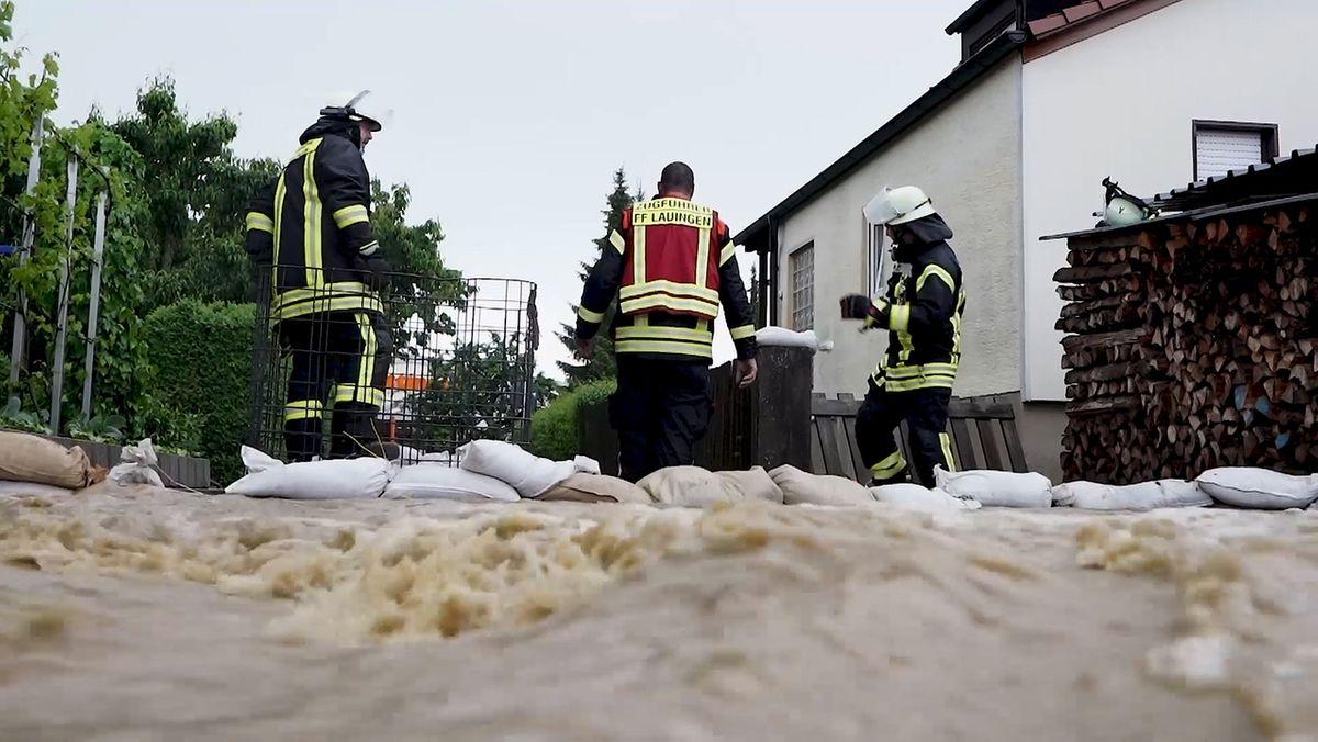 Blick auf zwei Feuerwehrmänner in einer überfluteten Straße in Wertingen am 6. Juni 2021.