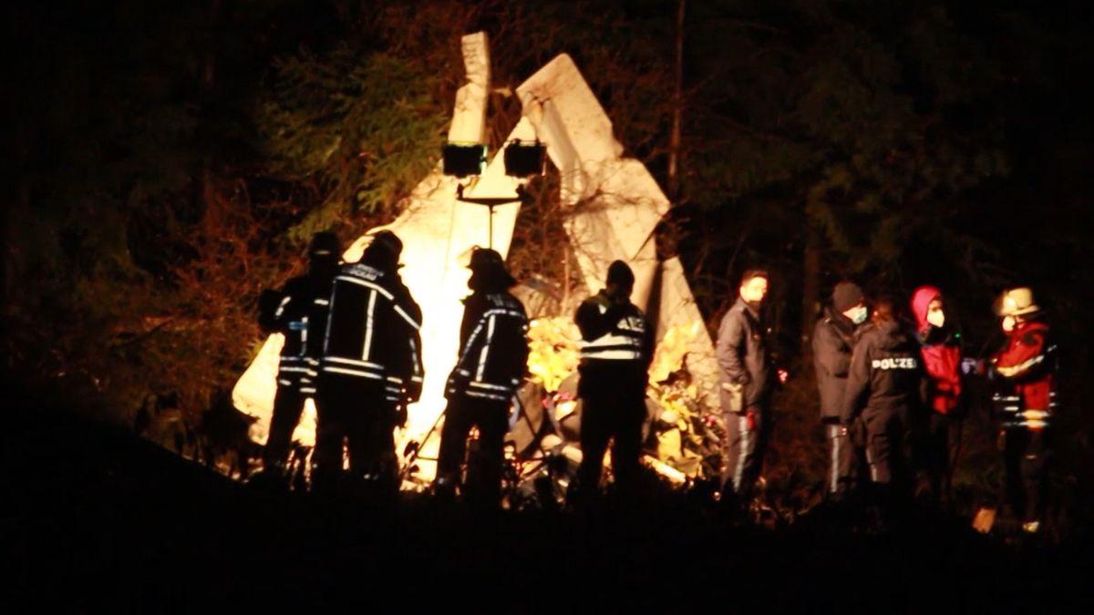 Einsatzkräfte stehen in einem Waldstück vor der hell beleuchteten Unfallstelle.