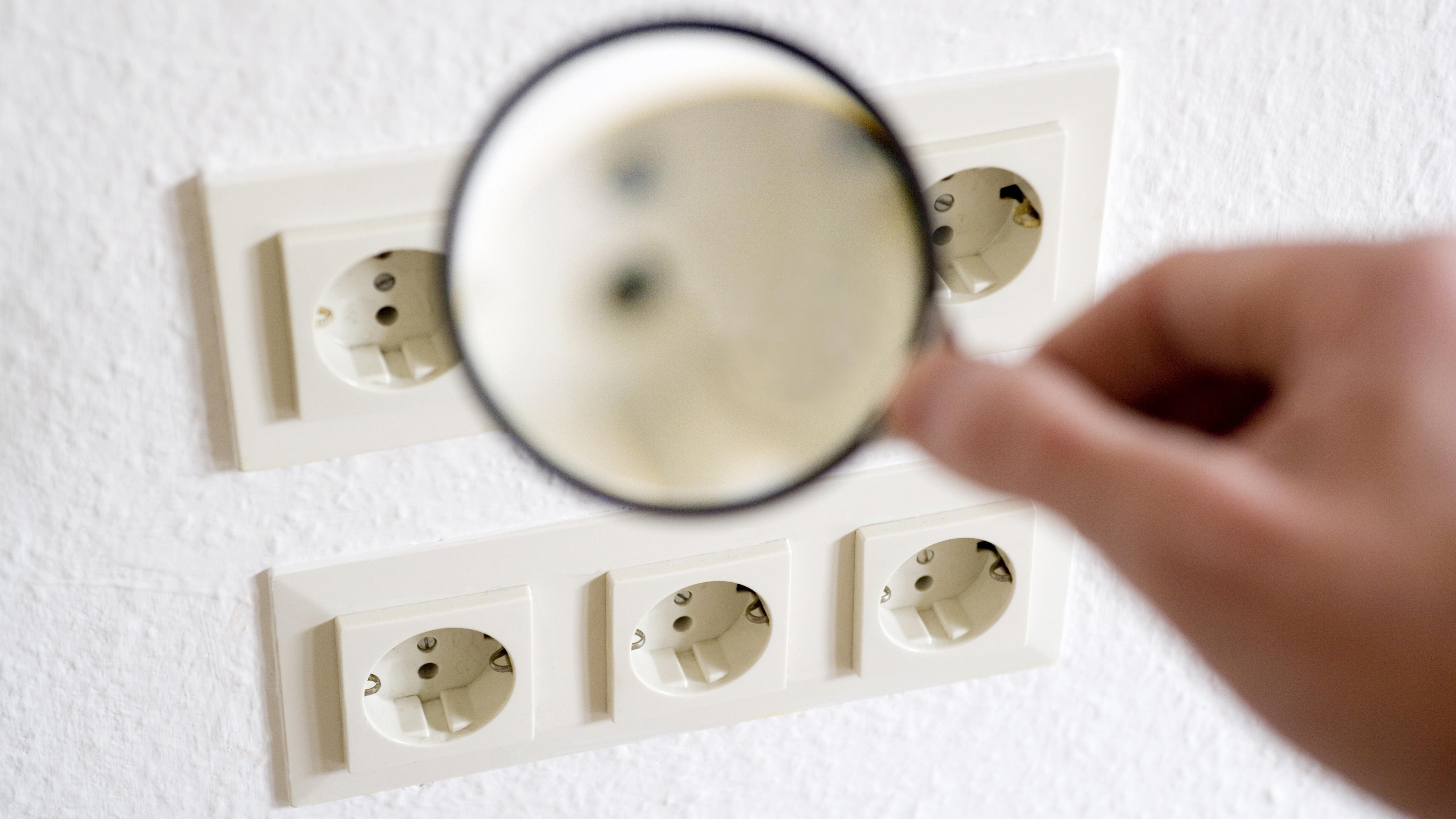 Kontrolle der Energieversorger: Lupe vor Steckdosen
