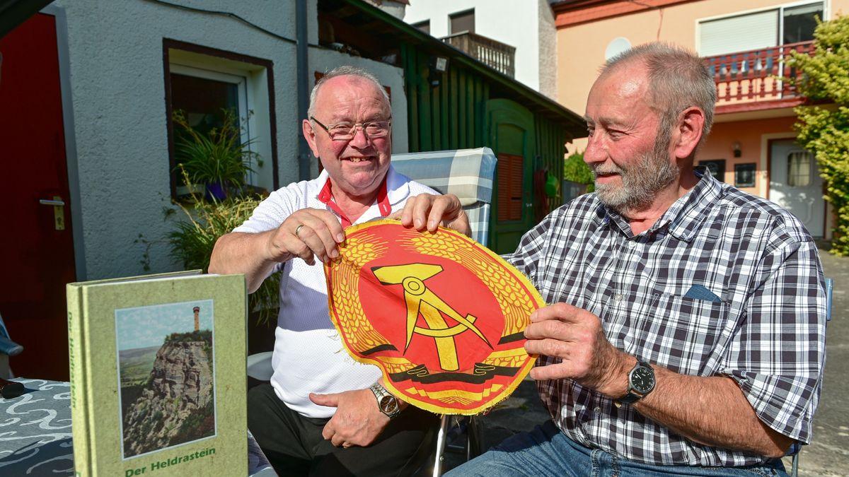 Zwei Männer zeigen einen Teil der DDR-Fahne mit Hammer, Zirkel und Ährenkranz.