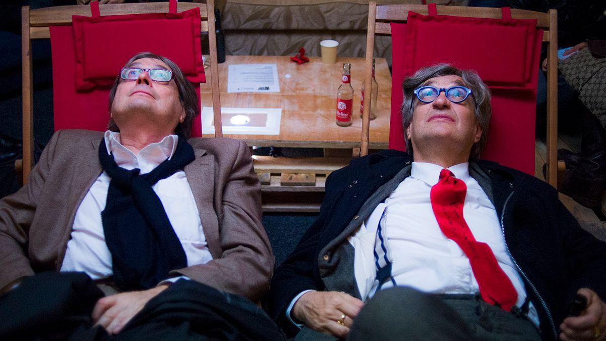 Wim Wenders und Heinz Badewitz sitzen auf Liegestühlen und schauen einen Film.