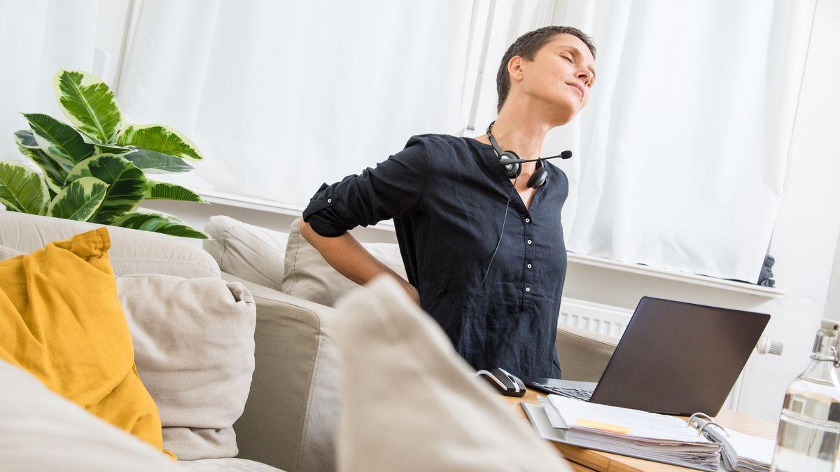Eine Frau im Homeoffice hat Rückenschmerzen