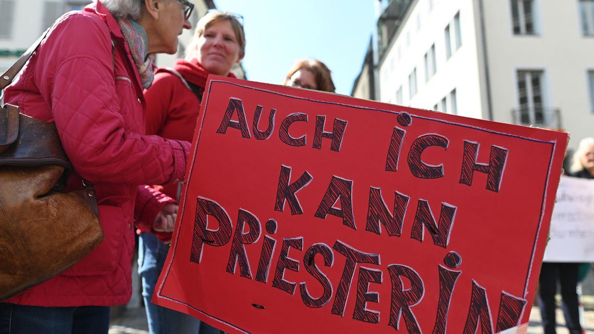 """Teilnehmer einer Protestaktion der Initiative Maria 2.0 der Katholische Frauengemeinschaft in der Erzdiözese Freiburg halten vor dem Münster ein Plakat mit der Aufschrift """"Auch ich kann Priesterin"""""""