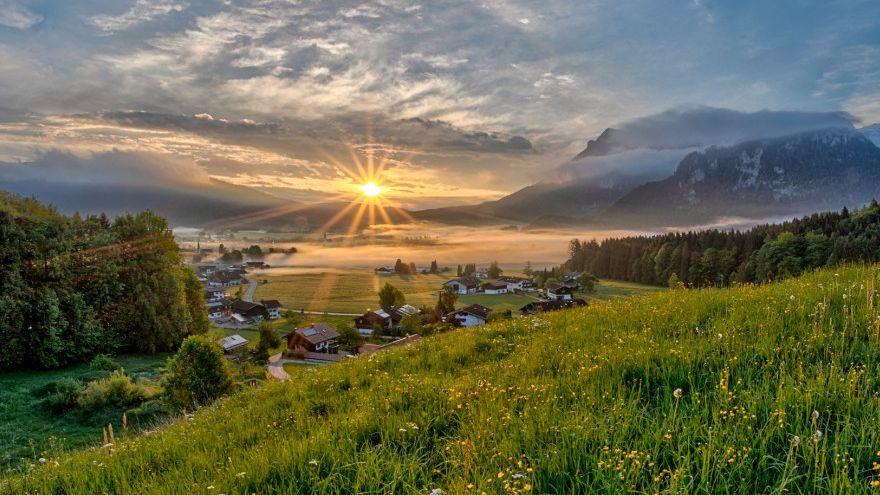 Sonne strahlt durch wolkenverhangenen Himmel über Inzell