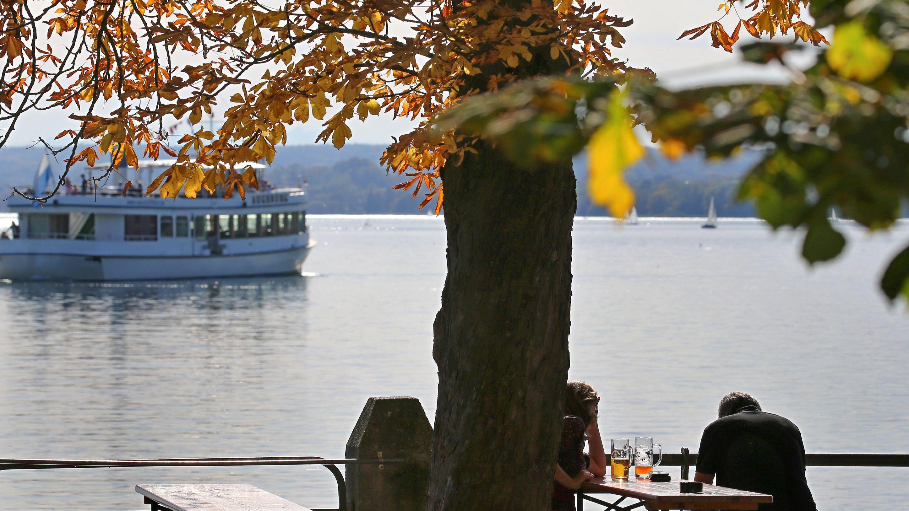 Ausflügler sitzen in einem Biergarten am Ammersee unter herbstlich gefärbten Bäumen