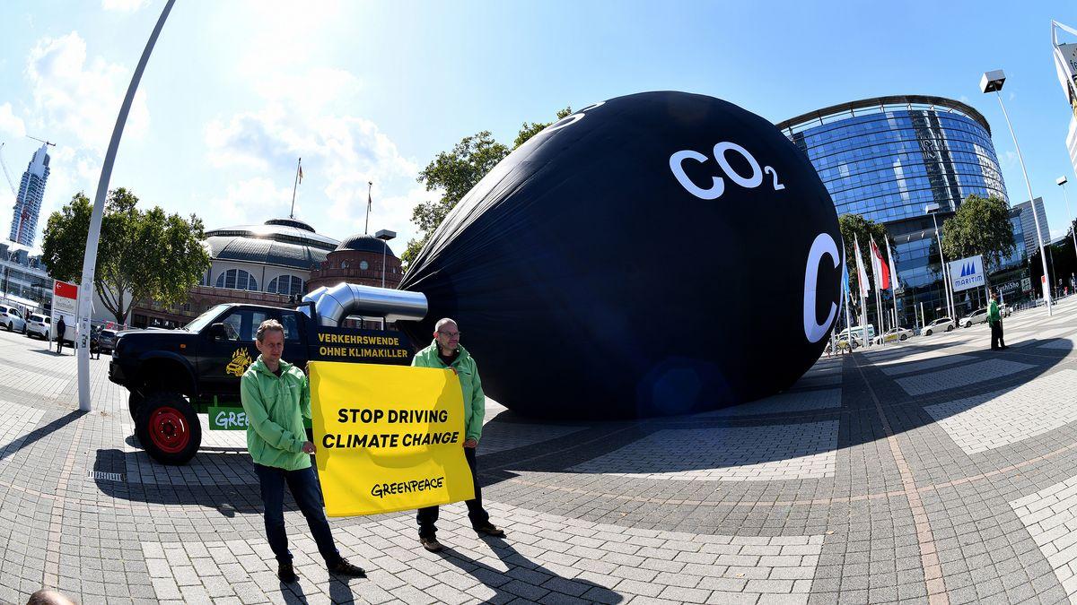Aktivisten der Umweltschutzorganisation Greenpeace machen vor dem Haupteingang der Internationalen Automobilausstellung IAA an der Messe in Frankfurt am Main auf den CO2-Ausstoss der Automobilindustrie aufmerksam.