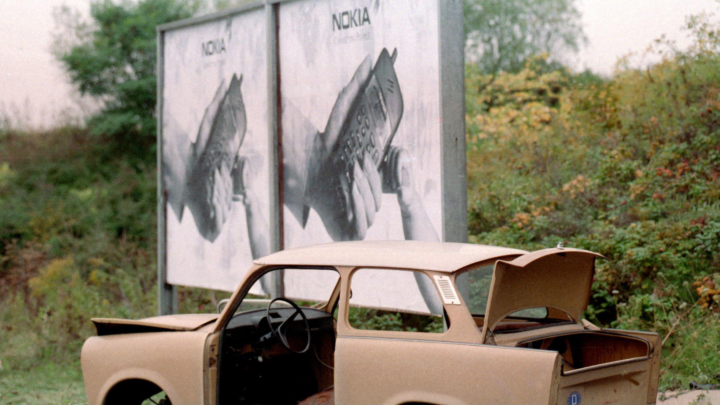 Ost-Berlin 1991: Trabbi-Karosserie vor Handy-Werbung