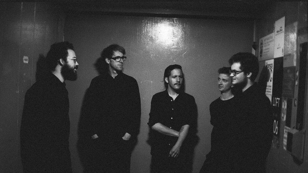 """Das Schwarzweißbild zeigt die fünf Mitglieder der Fusionband """"Fazer"""". An den Außenseiten, einander gegenüber: Martin brugger und Paul Brändle."""