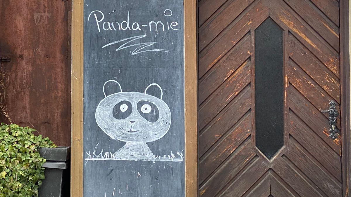 """Auf eine Tafel in Ebern wurde ein Pandabär gemalt, mit der Aufschrift """"Panda-mie""""."""