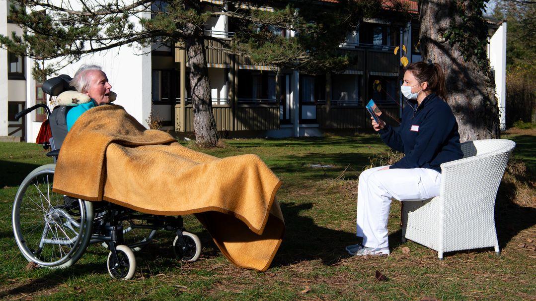 Eine Altenpflegerin liest im Garten eine Heims einer Bewohnerin vor, die in einem Rollstuhl sitzt.