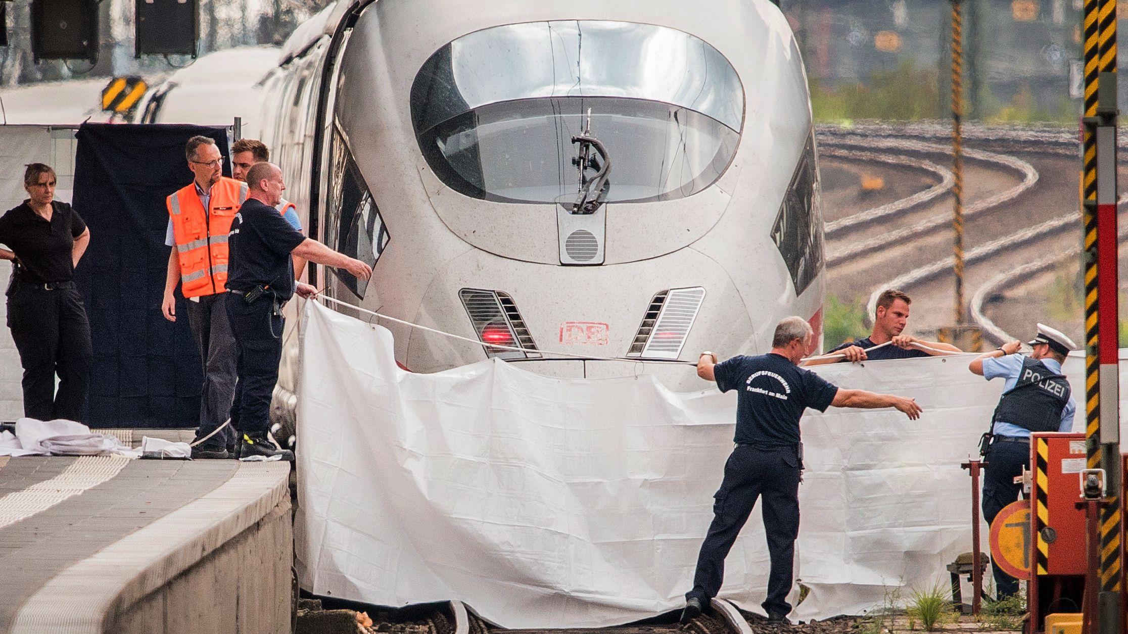 Polizisten und Feuerwehrleute spannen im Hauptbahnhof eine weiße Plane als Sichtschutz vor einen ICE. Ein achtjähriger Junge ist im Frankfurter Hauptbahnhof von einem Mann vor den einfahrenden ICE gestoßen und getötet worden.