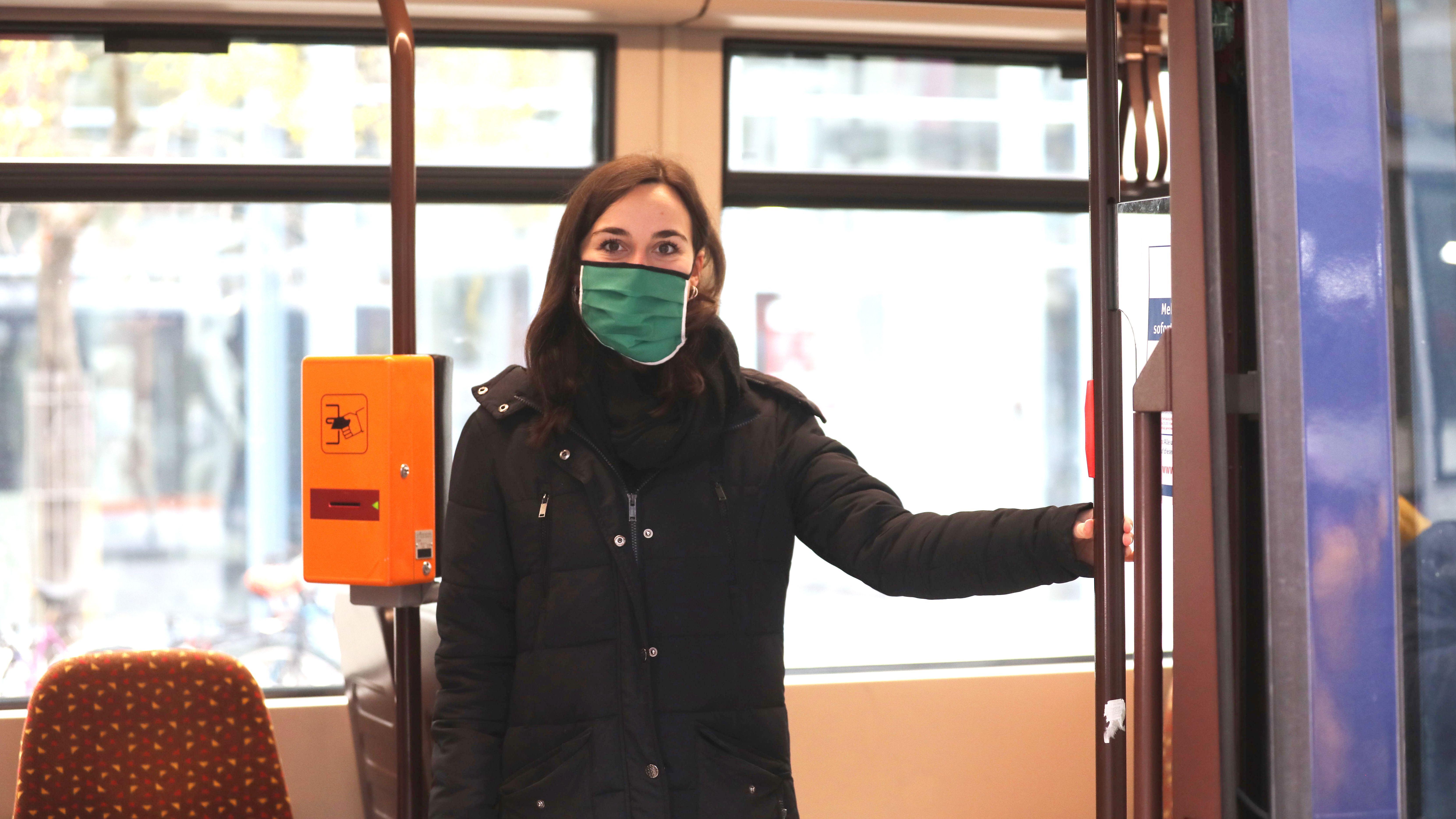 Junge Frau mit Mund-Nasen-Schutz in einer Straßenbahn (Symbolbild)
