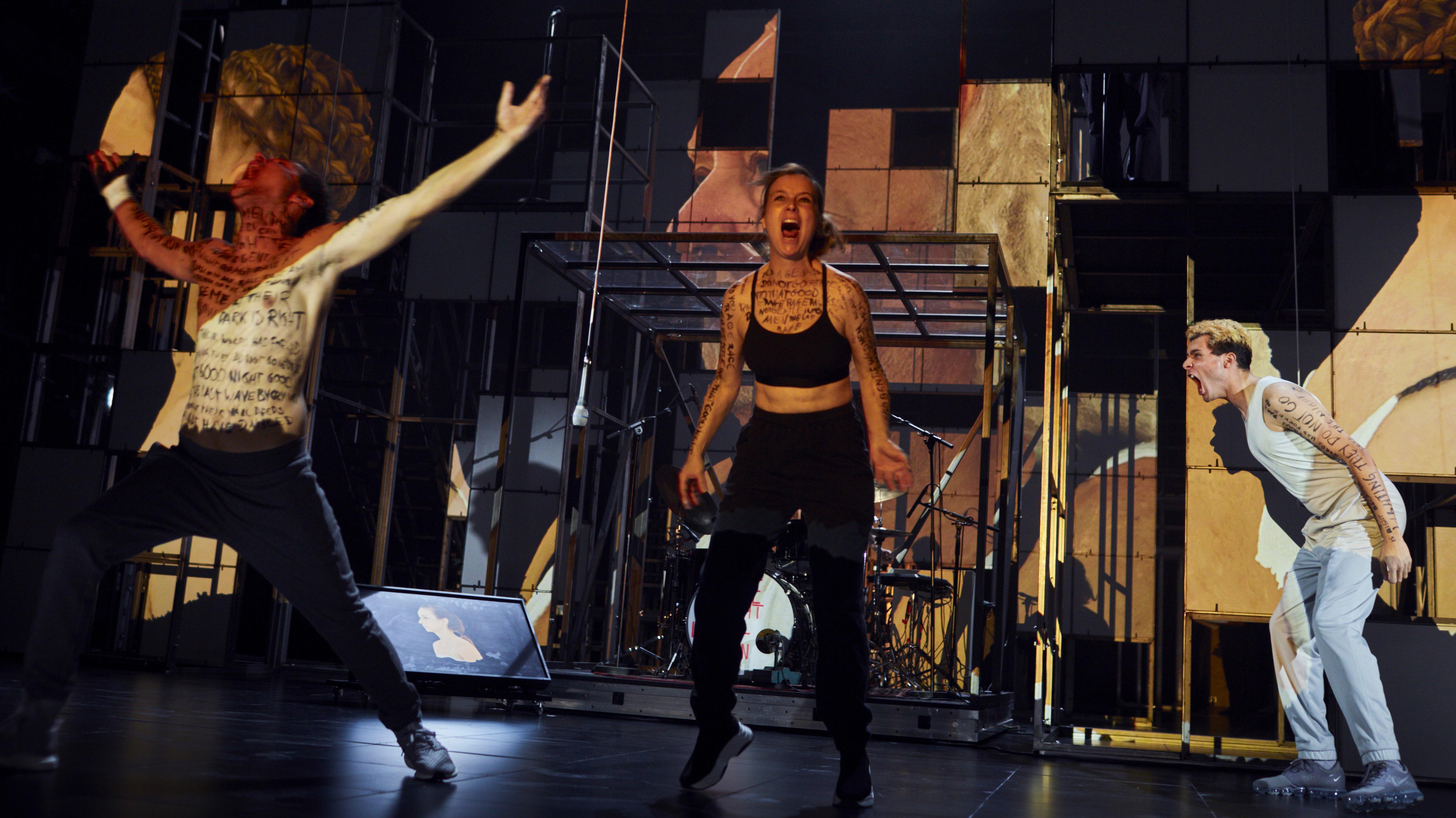 """Szene aus """"Dionysos Stadt"""" an den Münchner Kammerspielen. Zwei Männer und eine Frau schreien auf der Bühne."""